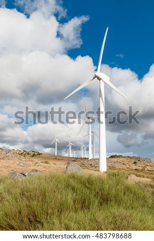 Wind turbines in motion over blue sky background