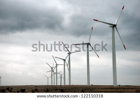 Wind turbines in row with stormy skies - stock photo