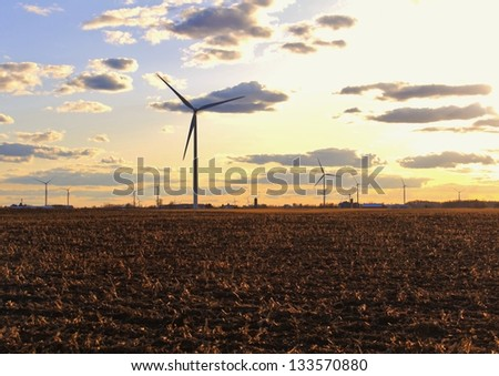 Wind turbines in rural Michigan with agricultural fields in the foreground. - stock photo