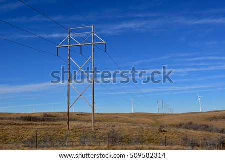 Wind turbines in the background with power lines carrying electricity in foreground.