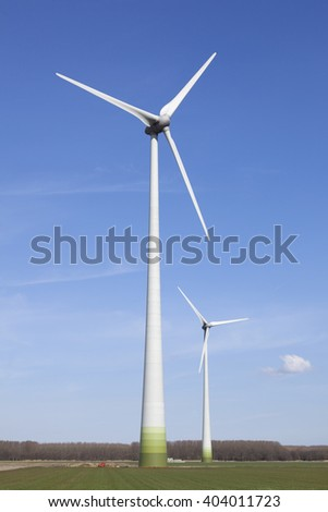 wind turbines in the dutch province of flevoland with blue sky in sunny weather.