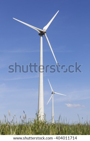 wind turbines in the dutch province of flevoland with grass and blue sky in sunny weather. - stock photo