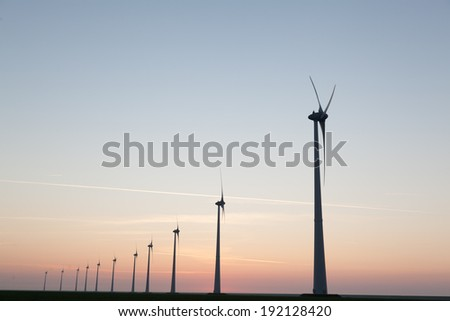 Wind turbines in the farmland during sunset - stock photo