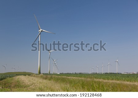 Wind turbines in the farmland with a clear blue sky - stock photo