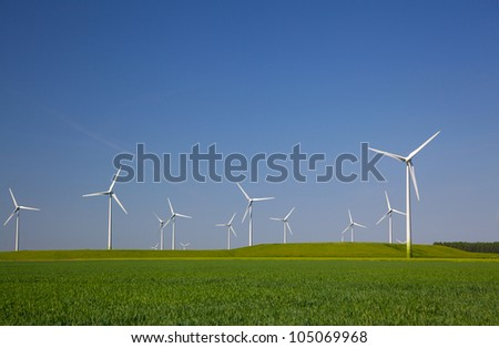 Wind turbines in the farmland with a clear blue sky in the Netherlands - stock photo