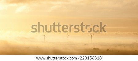 Wind turbines in the morning misty light - stock photo