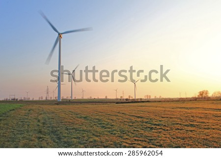 Wind turbines in the morning with dew on a meadows - stock photo