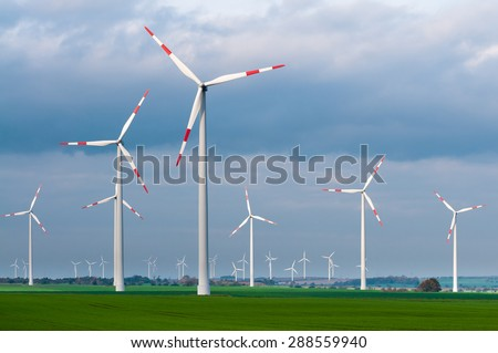 Wind turbines in the open countryside on windy day with dark clouds in the sky; Alternative power generation - stock photo