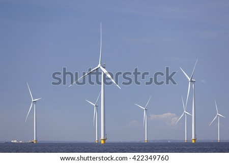 wind turbines in water of ijsselmeer off the coast of flevoland with blue sky in the netherlands - stock photo