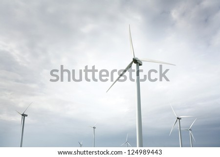 Wind Turbines in wind farm against cloudy sky