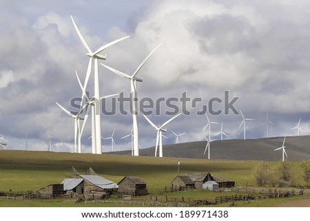 Wind Turbines in  Wind Farm Towering Over Cattle Ranch Buildings on Rollings Hills Along Columbia River in Washington State - stock photo