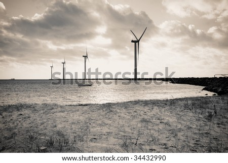 wind turbines offshore. Sea or ocean and beach with windmills producing renewable electric power - stock photo