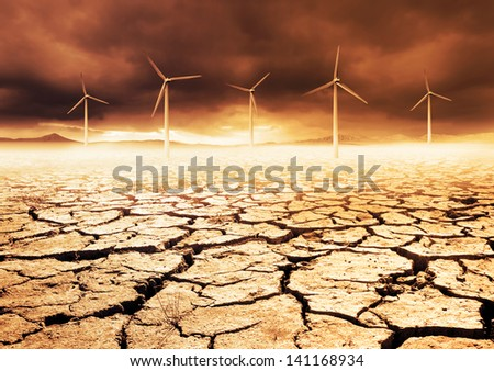 Wind Turbines on a cracked earth desert - stock photo