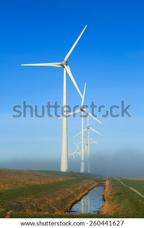Wind turbines on a dike generating clean energy on a foggy morning in the countryside.