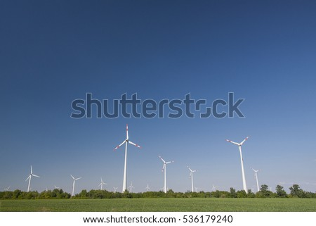 Wind turbines on agricultural land with blue sky