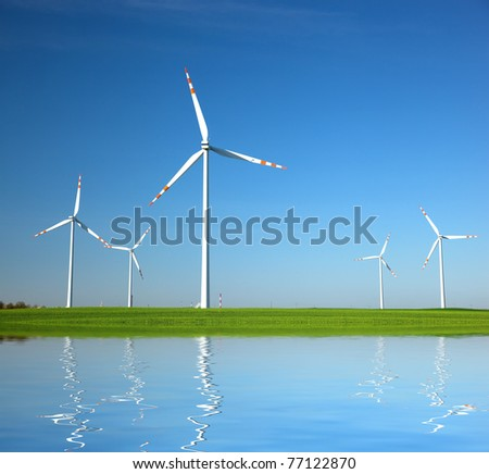 Wind Turbines on green field. Alternative energy, environment concept - stock photo