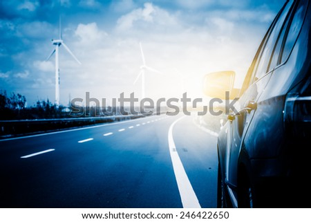Wind turbines on landscape along empty road against sky. - stock photo