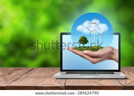 Wind turbines on meadow with tree holds in womans hand against blue sky and clouds in open laptop on wooden table. Worldwide Green energy concept - stock photo