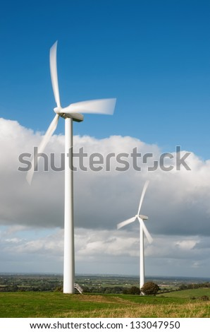 Wind turbines on the beautiful spring meadow. - stock photo