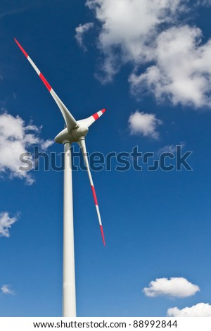 Wind turbines on the blue sky with clouds