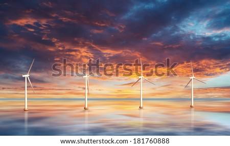 Wind turbines on water. Sunset - stock photo