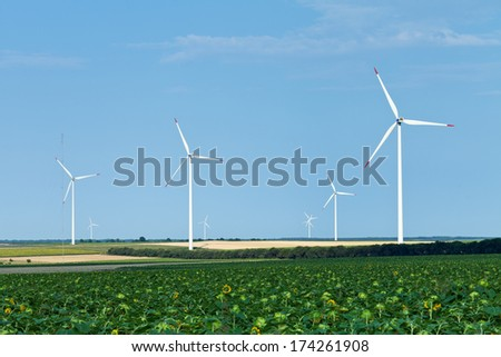 Wind turbines over sunflower and wheat fields in summer - stock photo