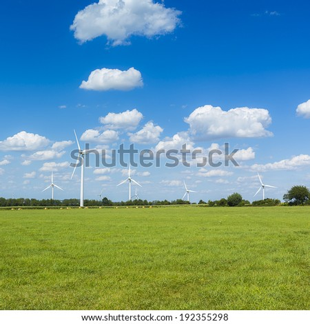 Wind turbines park Alternative Energy with cloudy blue sky on a meadow - stock photo