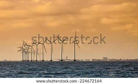 wind turbines power generator farm for renewable energy production along coast baltic sea near Denmark at sunset or sunrise. Alternative green energy ecology.