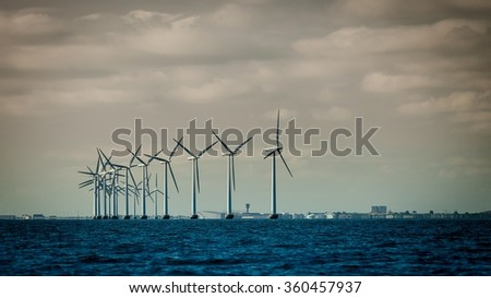 wind turbines power generator farm for renewable energy production along coast baltic sea near Denmark. Alternative green energy ecology.