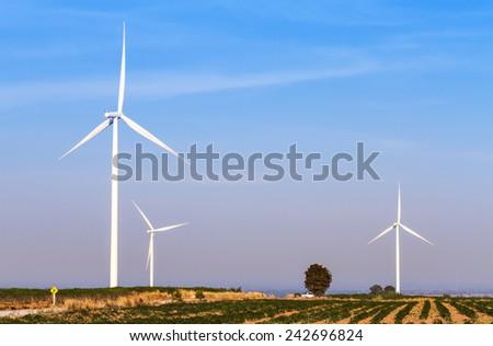 Wind turbines power generator on blue sky at farmer field - stock photo