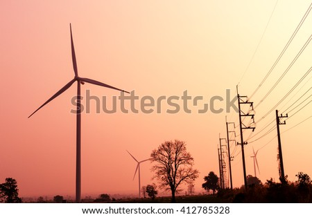 Wind turbines power generator on sunrise sky