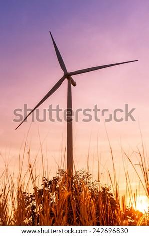 Wind turbines power generator on sunset at farmer field - stock photo