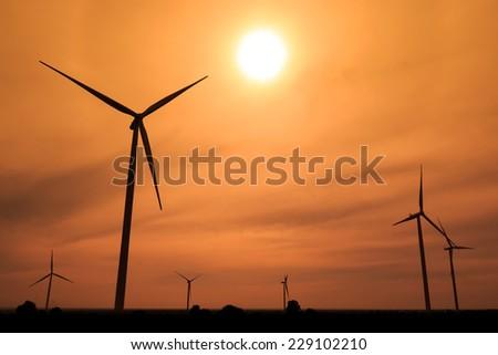 Wind turbines silhouette at sunset - stock photo