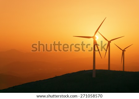 wind turbines silhouette on mountain at the sunset - stock photo