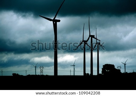 Wind Turbines Stormy Theme. Dark Stormy Theme with Many Wind Turbines Landscape. Technology Photo Collection. - stock photo