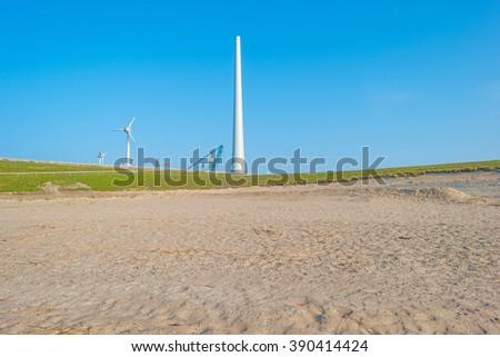 Wind turbines under construction along a lake - stock photo