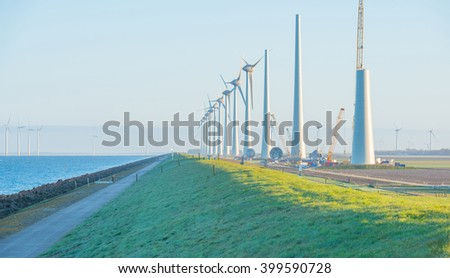 Wind turbines under construction along a lake