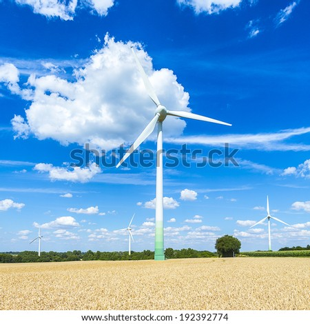 Wind turbines windpower park with cloudy sky on cornfield - stock photo