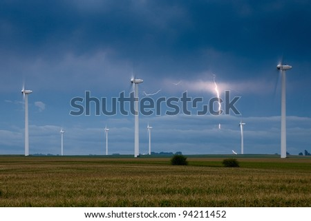 Wind turbines with a lightning bolt on the background - stock photo
