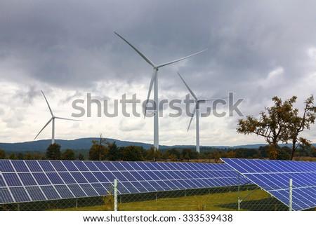 Wind turbines with solar panels - stock photo