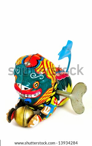 Wind-up toy dragon from China with blue tail and a golden ball in its paws, made of brightly-painted metal.  The winding key is visible in its side.