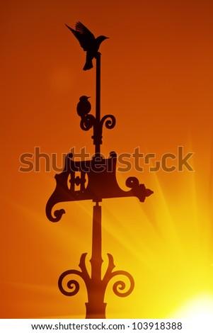 Wind Vane in Vivid Orange Colorful Sunrise Sky - stock photo