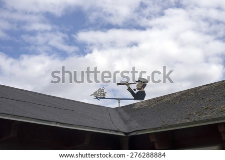 Wind Vane shaped as sailor / Old wind vane, painted iron, shaped sailor with binocular pointing on yacht - stock photo