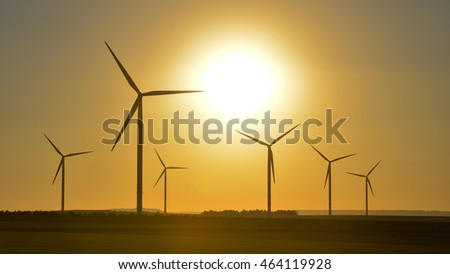 Wind wheels and a beautiful sunset seen in rural France, Europe