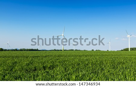 wind wheels in a field wind-turbine wind farm against blue sky agriculture - stock photo