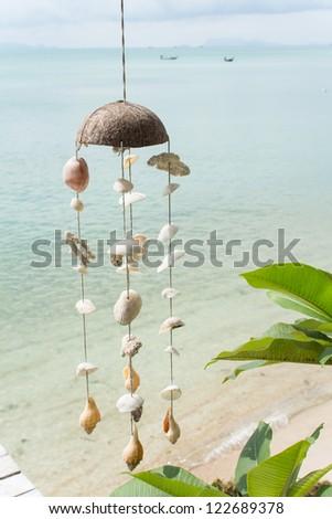 Windbell shell mobile on resort over ocean in Thailand - stock photo
