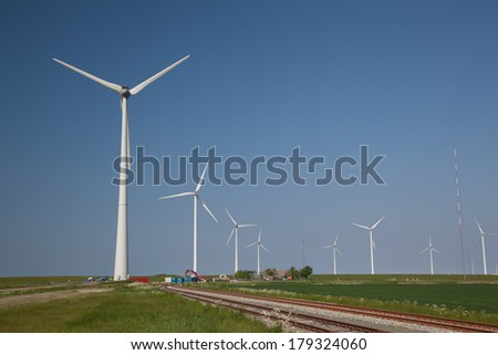 Windfarm with railroads and a clear blue sky - stock photo