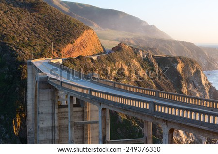 Winding arch bridge on coastal road next to Big Sur state park in sunset light with mountains and ocean on a back side. Cabrillo highway.  - stock photo