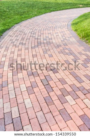 winding brick paved garden path with green grass by the side - stock photo