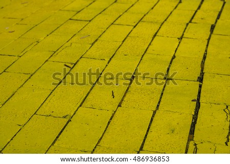 Winding bright yellow brick road with a shallow depth of field